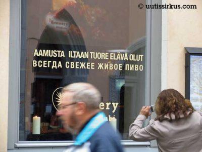 nainen ottaa kännykkäkuvaa tallinnalaisen olutravintolan näyteikkunasta