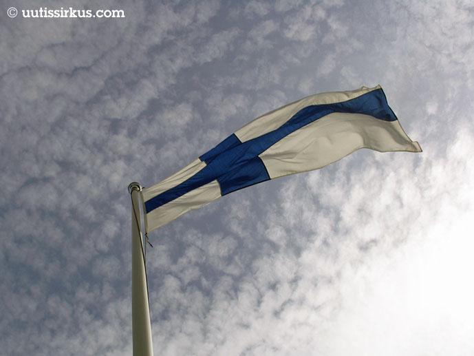 Suomen lippu liheuu tangossa puolipilvistä taivasta vasten