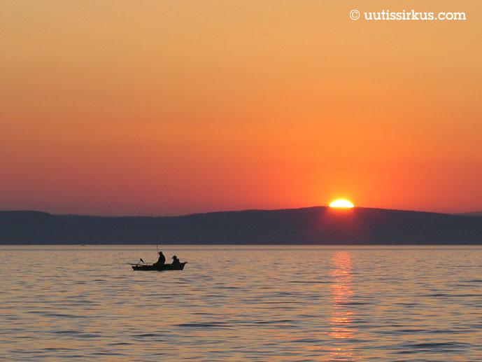 mies ja poika ongella veneessä, aurinko laskee metsän taakse taustalla