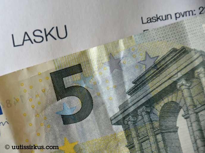 viiden euron seteli laskulomakkeen päällä