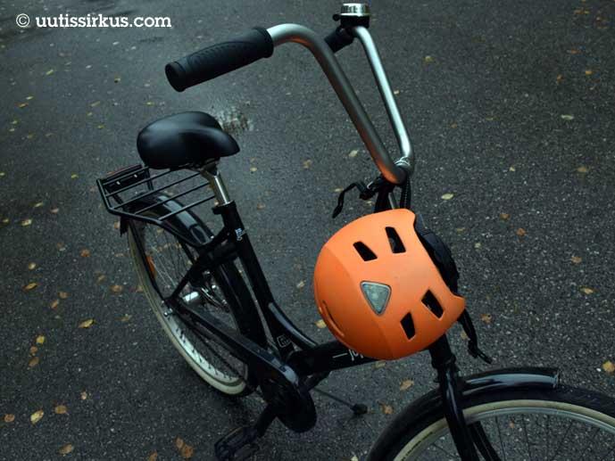 oranssi pyöräilykypärä pysäköidyn Jopon ohjaustangossa