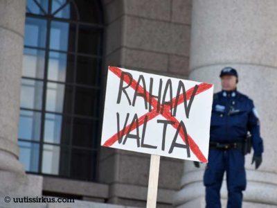 eduskuntatalon portailla rahan valta -mielenosoituskyltti, jonka takana poliisi