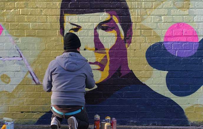 Poika maalaa Spok-aiheista graffitia tiiliseinään