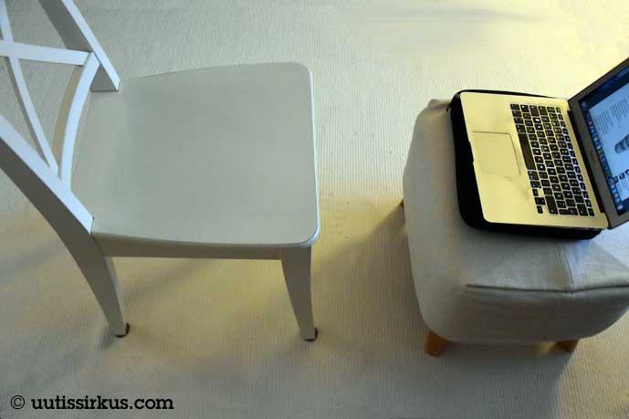 Valkea ruokapöydän tuoli ja rahi, jolla läppäri, kaiken alla valkoinen matto