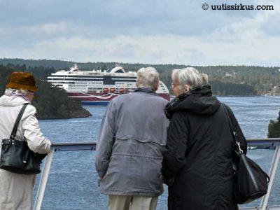 kolme eläkeläistä seisoo Ruotsin-laivan kannella ja katselee vastakkaiseen suuntaan seilaavaa toista matkustaja-alusta