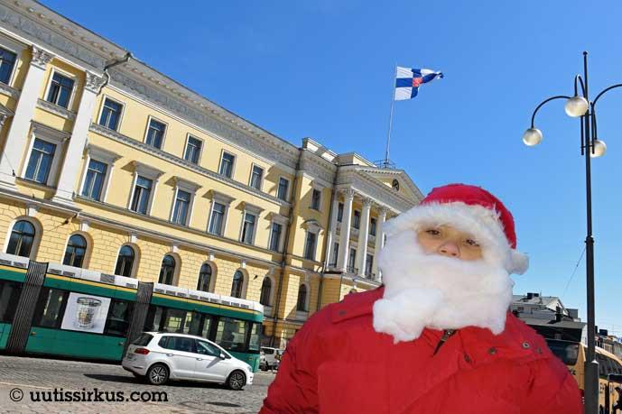 joulupukki seisoo valtioneuvoston linnan edessä, linnan katolla liehuu Suomen lippu