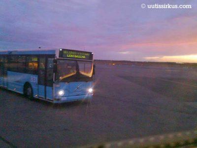 sininen lentokenttäbussi ajaa aamun sarastuksessa kentällä