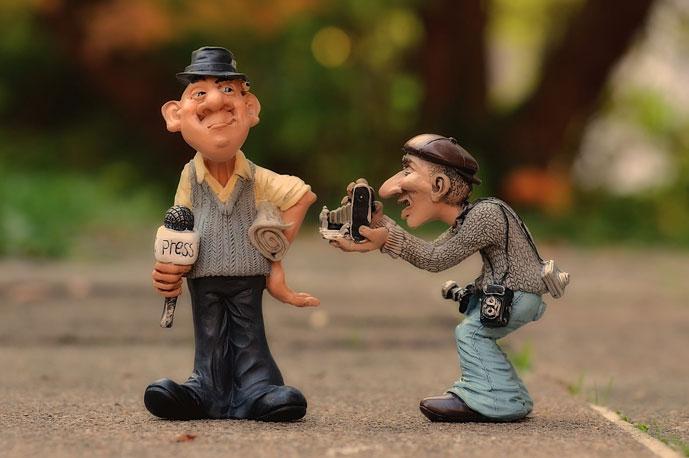 savinuket: toimittaja, jolla mikrofonissaan press-kyltti, useammalla kameralla varustautunut kuvaaja ottaa hänestä kuvan