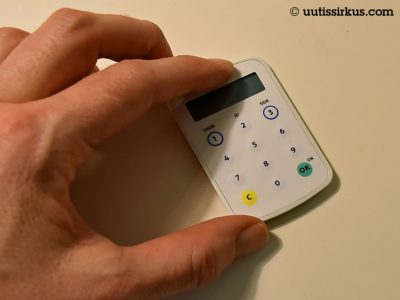 luottokortin kokoinen taskulaskinta muistuttava tunnuslukulaite vasemman käden peukalon ja eyusormen välissä