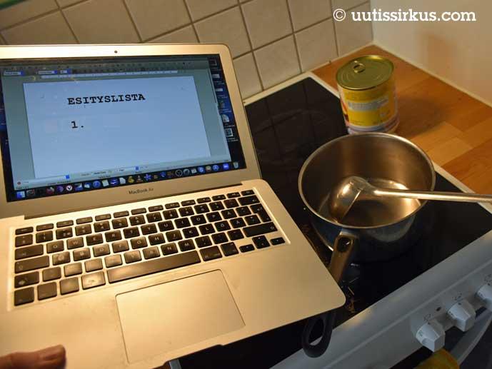 Hellalla kattila ja hernekeittopurkki, etualalla kokkaajan ksäi, jossa läppäri. Läppärin ruudulla teksti: Esityslista.