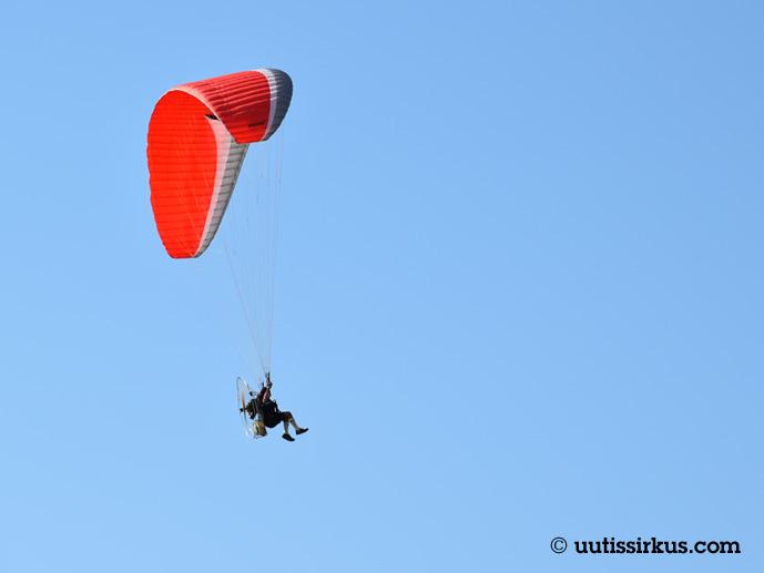 mies lentää lentovarjolla, istuu tuolissa moottori selässään