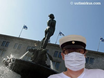 mies hengityssuojaimessa ja ylioppilaslakissa Havis Amandan edustalla