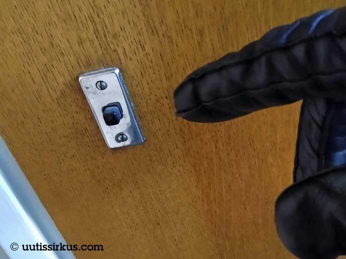 mustaan hanskaan verhottu sortmi lähestymässä ovikellon nappulaa