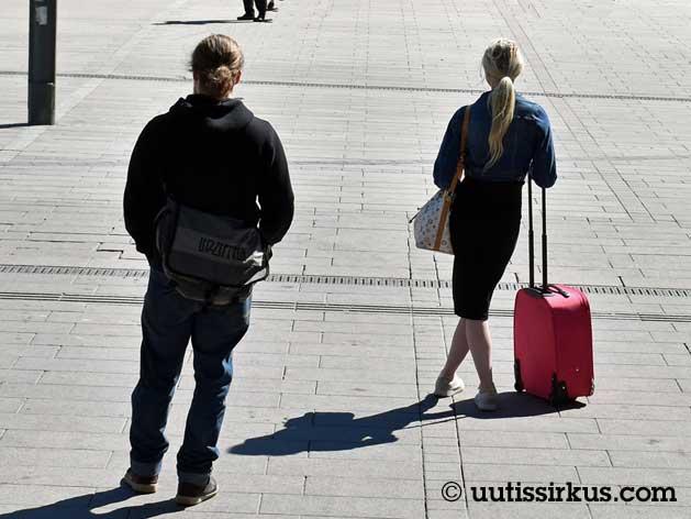 torilla kaksi nuorta aikuista, selin kameraan, mies ja nainen, nainen nojaa matkalaukkuun