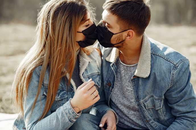 nainen ja mies suutelevat maskit kasvoillaan