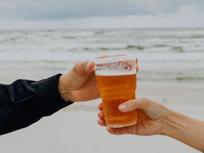 Miehen käsi ja naisen käsi oluttuopilla, takana meren aallot, kuva Karolina Grabowska / Pexels