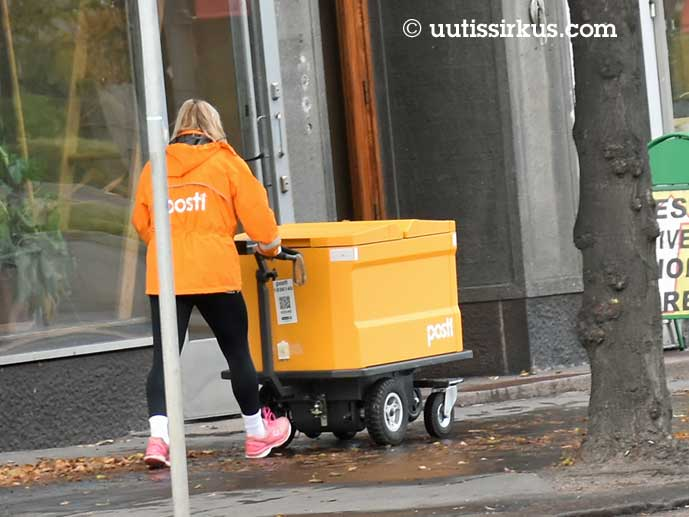 nainen työntää postikärryjä kadulla