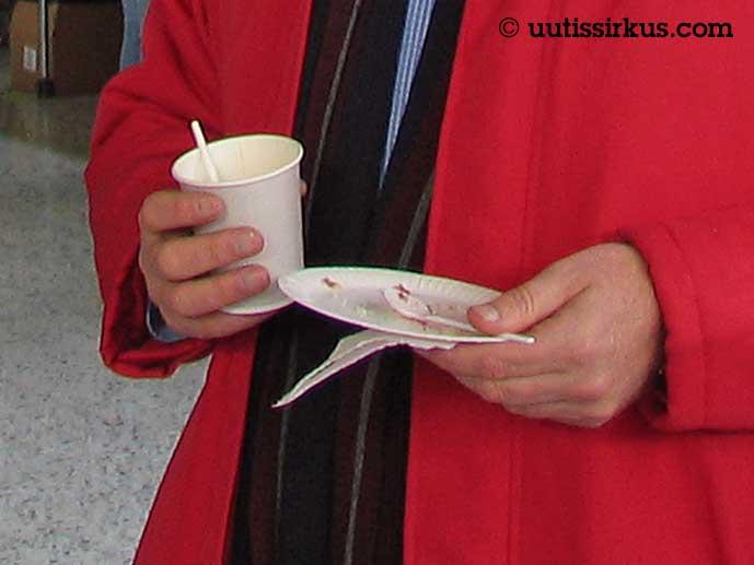 mies pahvikuppi ja -lautanen kädessään