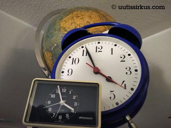 iso ja pieni herätyskello karttapallon vieressä