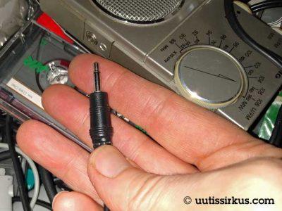 monoliitin sormien päälle, alle pöytälaatikon sekalaisia johtoja ja yksi C-kasetti, vieressä pieni matkaradio