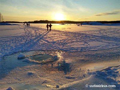 ulkoilijoita Aurinkolahden jäällä, etualalla avanto