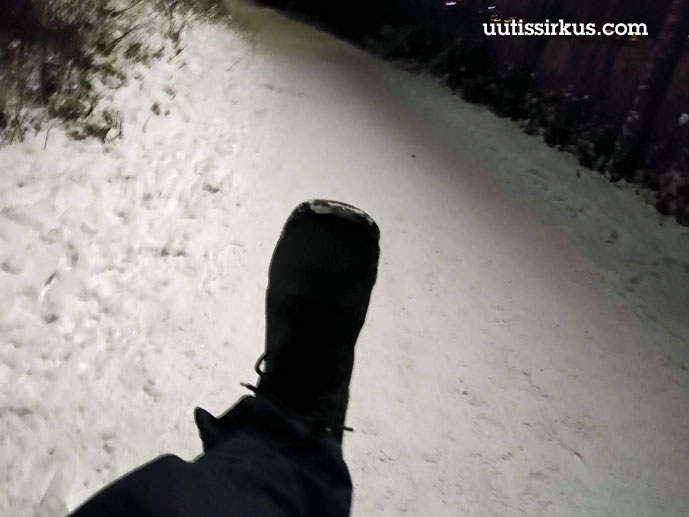 musta kenkä osumassa lumisen liikuntareitin pintaan