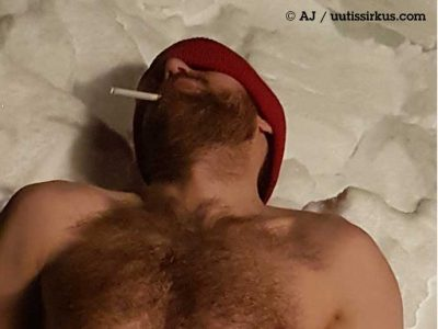 mies makaa lumihangessa pipo päässä ilman paitaa, tupakki suussa