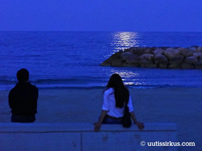 Erillään istuva pariskunta katselee kuunsiltaa