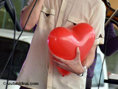 mies mikrofonissa, hänen toisessa kädessään iso sydämenmuotoinen ilmapllo, jota hän painaa rintaansa vasten