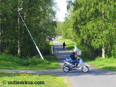 kylänraitilla yksi mopo, yksi polkupyörä ja yksi vino lyhtypylväs