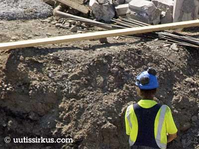 rakennusmies silmäilee työmaalla lautaa