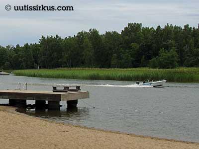 laituri hiekkarannalla, vene menee taustalla salmessa