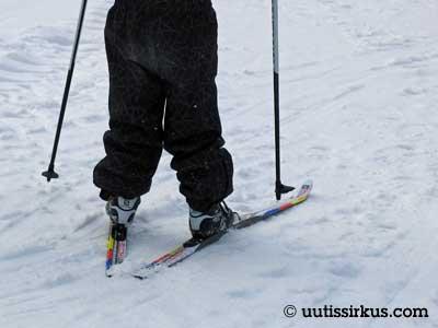 ihminen hiihtää leveät housut jalassaan