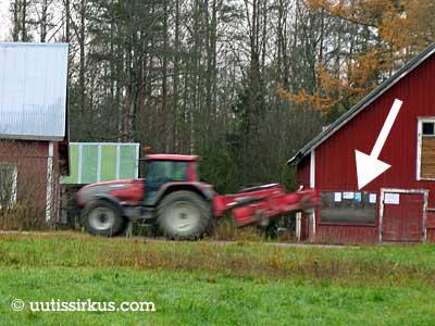 traktori ajaa punamallalla maalatun liiterin seinöässä olevan ilmoitustaulun ohitse