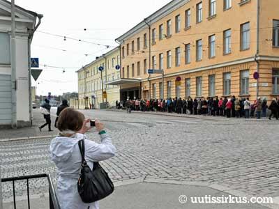 ihmiset jonottavat presidentinlinnaan Helsingin Mariankadulla