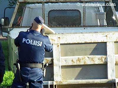 poliisi seisoo nuhjuisen lava-auton vieressä