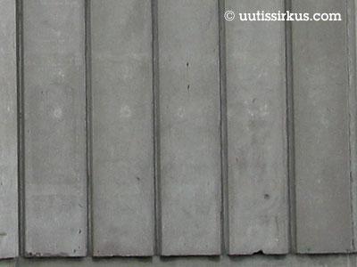 harmaista kapeista betonielementeistä tehty seinä