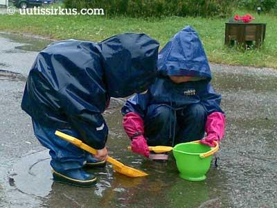 kaksi lasta siniset kurapuvut yllään lapioi keltaisella lapiolla vettä vesisateessa lätäköstä