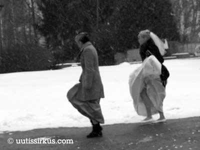 tuuli nostaa naisen hääpuvun helmaa räntäsateessa