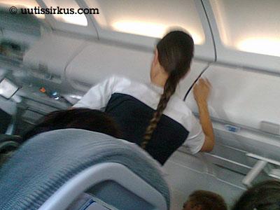 lentoemäntä asettaa matkatavarahyllyn luukkua kiinni
