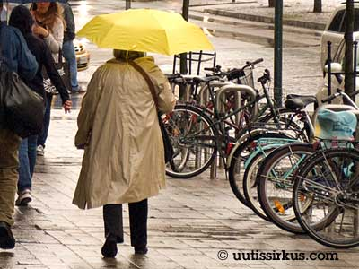 eläkeläinen kävelee keltaisen sateenvarjonsa alla