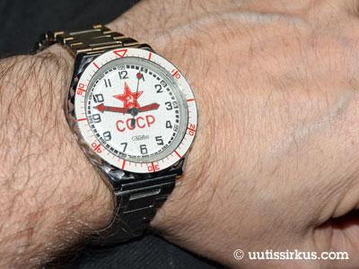 miehen kädessä kello, jonka taulussa sirppi ja vasara ja cccp-teksti