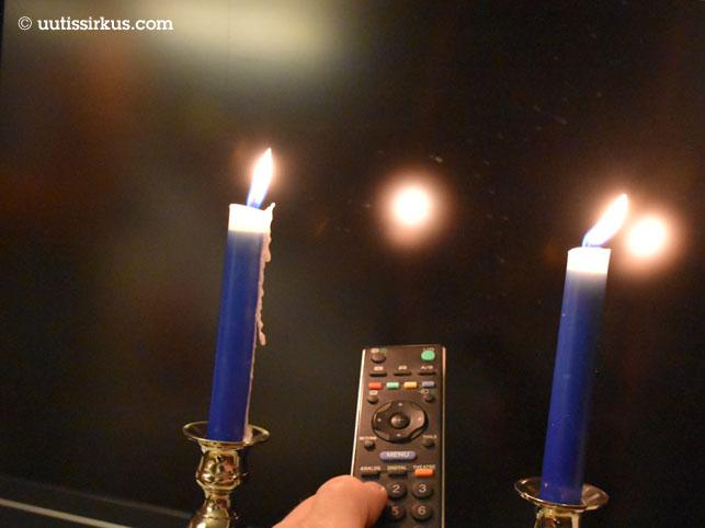 television edessä kaksi kynttilää ja niiden välissä käsi, jossa kaukosäädin