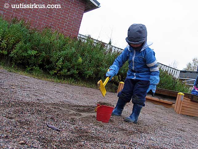 lapsi lapioi soransekaista hiekkaa ämpäriin