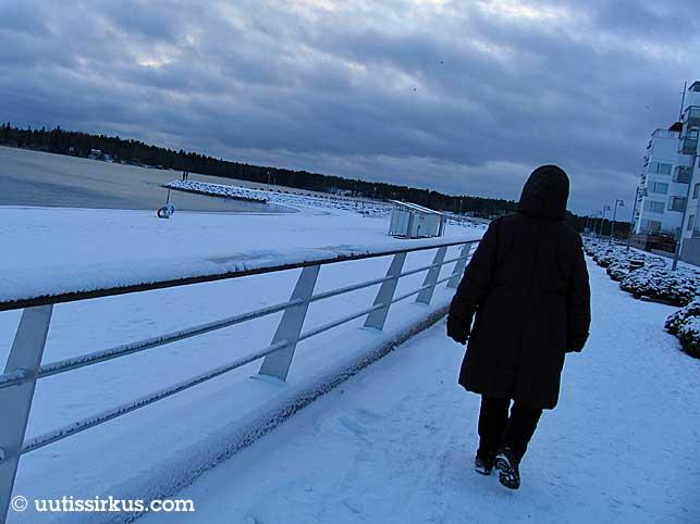 mustapomppainen nainen kävelee harmaan taivaan alla talvisella rantabulevardilla