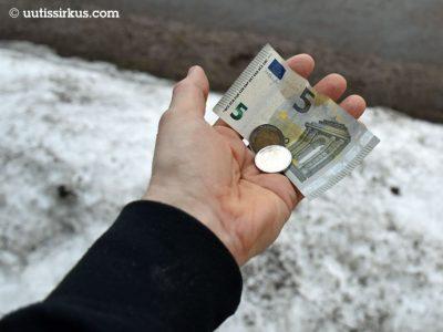 Miehen paljaassa kourassa 5 euron seteli ja kaksi kahden euron kolikkoa