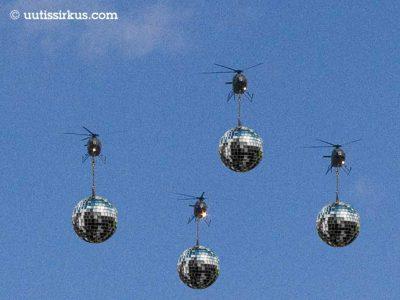 neljä lähestyvää helikopteria sinitaivasta vasten, koptereista roikkuvat suurikokoiset diskopallot