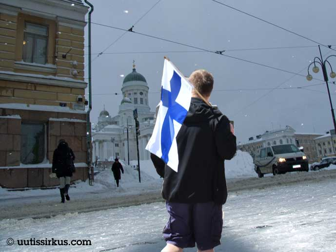 mies kävelee shortseissa Suomen lippu olallaan kohti talvista Senaatintoria