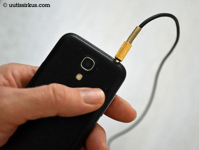 käsi, jossa älypuhelin, josta lähtee kuulokkeen johto