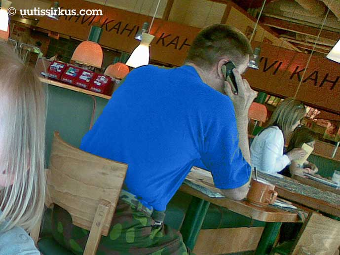 siilitukkainen mies istuu kahviossa maastohousut jalassa, sinisessä t-paidassa, puhuu puhelimeensa